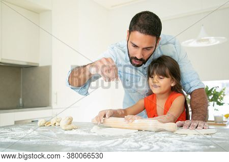 Cheerful Girl And Her Dad Kneading And Rolling Dough On Kitchen Table With Flour Messy. Father Teach