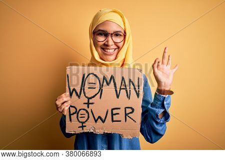 Beautiful woman with curly hair wearing muslim hijab asking for women rights holding banner doing ok sign with fingers, excellent symbol