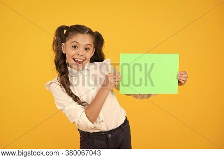Look Here. Girl School Uniform Hold Poster. Back To School Concept. Schoolgirl Pupil Show Poster. Sc