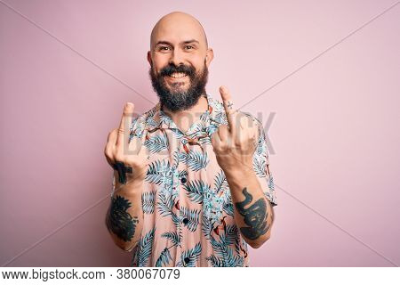 Handsome bald man with beard and tattoo wearing casual floral shirt over pink background Showing middle finger doing fuck you bad expression, provocation and rude attitude. Screaming excited