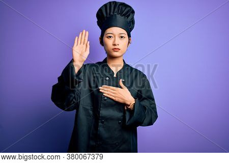 Young beautiful chinese chef woman wearing cooker uniform and hat over purple background Swearing with hand on chest and open palm, making a loyalty promise oath