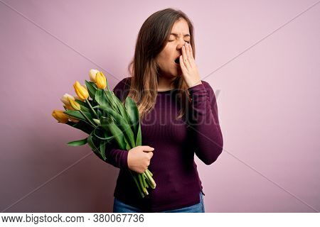 Young blonde woman holding romantic bouquet of yellow tulips flowers over pink background bored yawning tired covering mouth with hand. Restless and sleepiness.