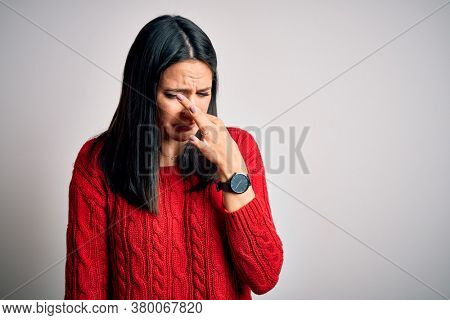 Young brunette woman with blue eyes wearing casual sweater over isolated white background smelling something stinky and disgusting, intolerable smell, holding breath with fingers on nose. Bad smell