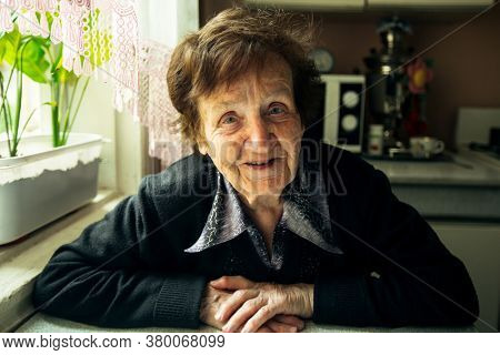 Portrait of a smiling old woman in her house.