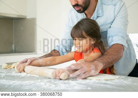 Happy Girl And Her Dad Rolling Dough On Kitchen Table With Flour Messy. Father Teaching Daughter To