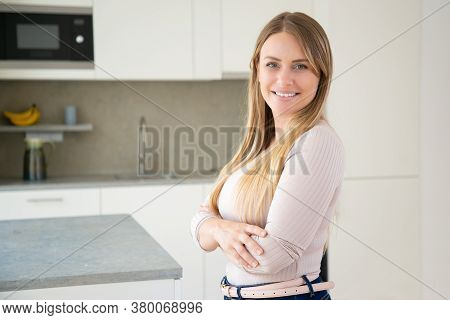 Cheerful Attractive Fair Haired Young Woman Posing With Arms Folded In Kitchen, Looking At Camera An