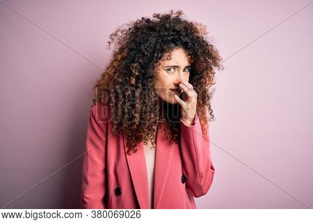 Young beautiful businesswoman with curly hair and piercing wearing elegant jacket smelling something stinky and disgusting, intolerable smell, holding breath with fingers on nose. Bad smell