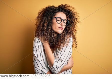 Young beautiful woman with curly hair and piercing wearing striped shirt and glasses Hugging oneself happy and positive, smiling confident. Self love and self care