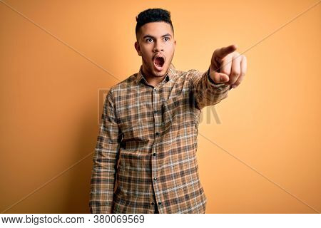 Young handsome man wearing casual shirt standing over isolated yellow background Pointing with finger surprised ahead, open mouth amazed expression, something on the front