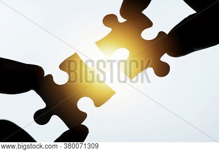 Closeup Of Hand Holding And Connect Jigsaw Puzzle With Sunlight. Business Corporate Solution Problem