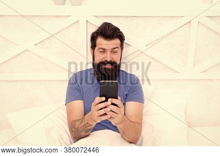 Video Call Concept. Cellular Communication. Modern Guy Talking On Smartphone In Bed. Handsome Man Wi