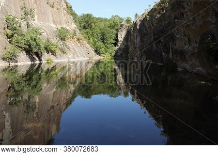 View Of A Flooded And Old Limestone Mine With Beautiful Reflections Of Rocks And Trees.