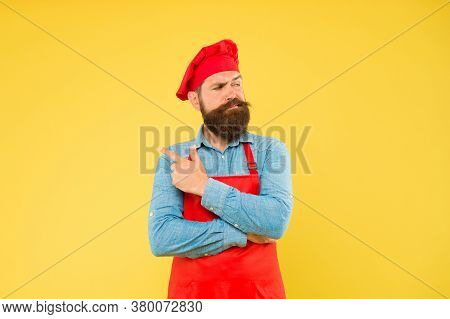 Giving A Catering Solution. Bearded Chef Pointing Finger. Brutal Male Cook In Hat And Apron. Profess