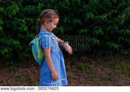 Kid Using Smartwatch Outdoor. Child Talking On The Smartphone. Schoolgirl Using Touchscreen On Watch