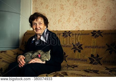 An old russian woman with her cat at the home.
