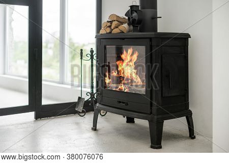 Fireplace At Lounge Room Standing On Concrete Floor With Copy Space. Home With Modern Interior, Wood