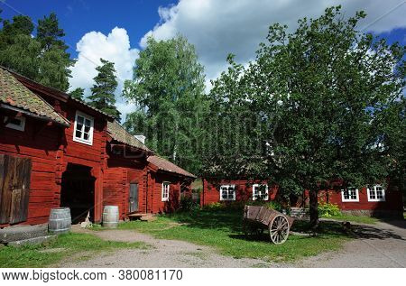 Swedish traditional wooden red houses in Vallby open-air Museum. Vasteras, Sweden. Village houses and old cart on green grass under big tree on yard. Summer sunny day