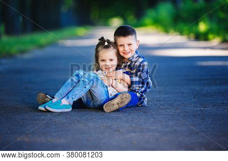 Childrens Love, A Little Boy And A Girl, Having Fun, Laugh And Smile, Kiss And Sits Outdoors