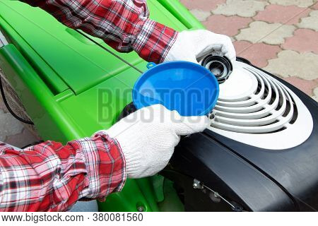 Male Checking The Fuel Level In Lawn Mower. A Green Lawnmower. Gardening. Maintenance Of Equipment.