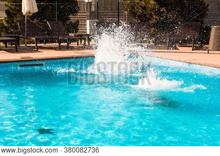 Pool Fun. Jumping Into The Outdoor Swimming Pool With Clear Blue Water