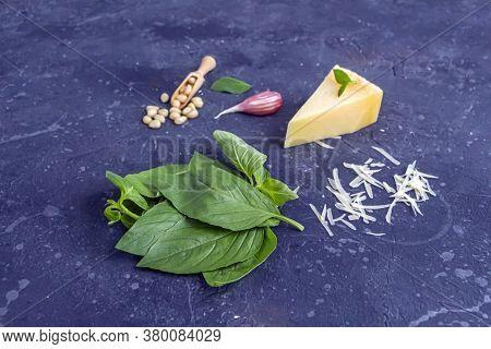 Fresh Ingredients For Pesto On Dark Background. Basil Leaves, Pine Nuts, Garlic, Parmesan And Olive