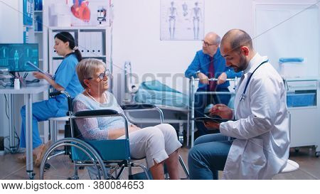 Doctor Consultation In Recovery Clinic With Elderly Woman In Wheelchair And Senior Man With Disabili