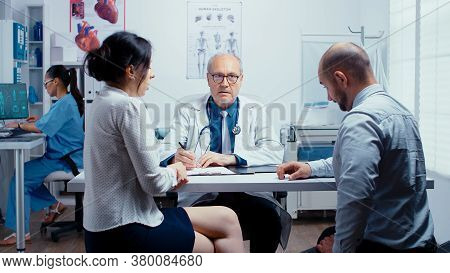 Young Couple Talking With Senior Doctor In Modern Private Clinic. Family Planning Specialist. People