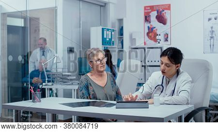 Doctor Filling Out Prescription On Digital Tablet While Consulting Elderly Senior Retired Woman. Hea
