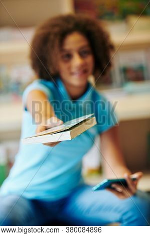 Curly Teenage Girl Outstretching Hands With Book To Camera, Selective Focus