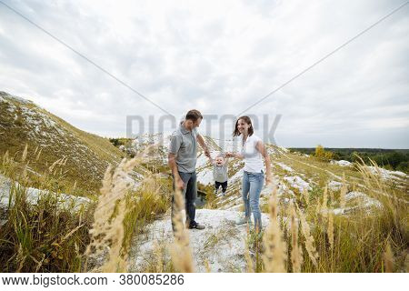 Mom, Dad Hugging Son In The Sand Mountains Enjoy And Look At Nature. Young Family Spending Time Toge