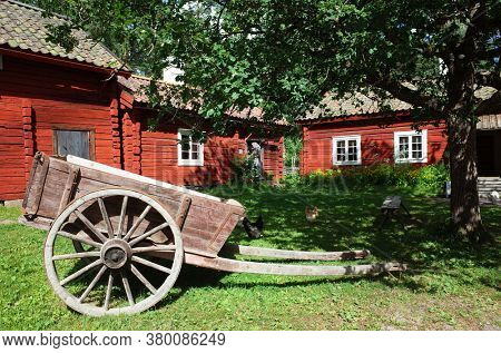 Old wooden cart on big wheels on green grass in yard surrounded by Swedish traditional red houses in Vallby open-air Museum. Vasteras, Sweden. Summer sunny day