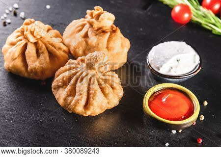 Appetizing Traditional Fried Dumplings On A Dark Background Among And Sauces. Traditional Food Conce