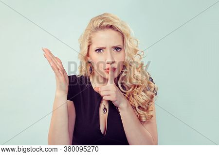 Pretty Blond Woman Holding Finger On Lips Looking At Camera In Discontent