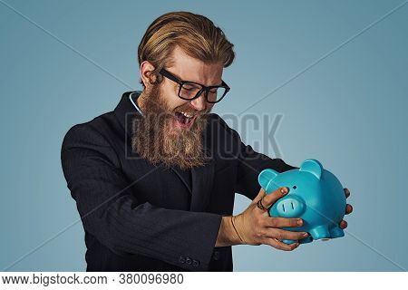Unhappy Man In Glasses Angry At His Piggy Bank Trying To Broke It Up, Bearded Hipster Businessman Is
