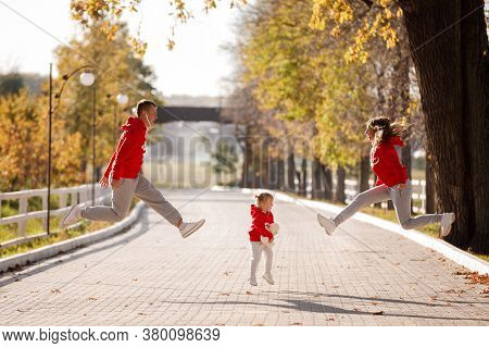 Father, Mother And Little Daughter Are Jumping In The Autumn Park, Happy Family Is Having Fun Outdoo