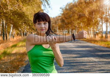 White Young Fitness Woman, Wearing A Smartwatch Activity Tracker, Stretching Her Arms - Tricep And S