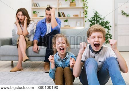 Kids Bad Behavior Problems. Children Shouting Loudly While Tired Parents Covering Ears Sitting On So