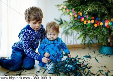 Cute Baby Girl And Kid Boy Taking Down Holiday Decorations From Christmas Tree. Children, Siblings,