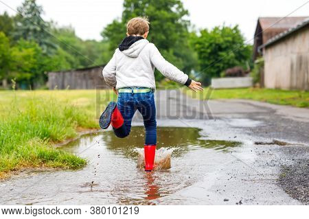 Happy Kid Boy Wearing Red Rain Boots And Walking During Sleet And Rain On Rainy Cloudy Day. Child In