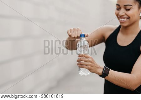 Vital Energy, Water And Sport. Happy African American Girl In Sportswear With Modern Headphones And