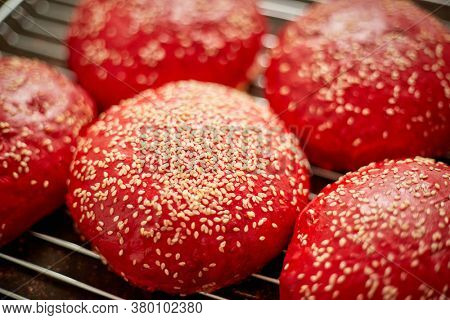 Fresh baked red homemade burger buns with sesame top view. Placed on metal grill. Flat lay.