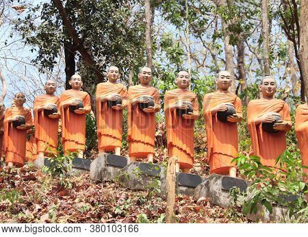 Row statues of buddhist monks with alms bowl in Dhama-Tibhathana temple (Dhama Dialogue Place), Cambodia, Asia