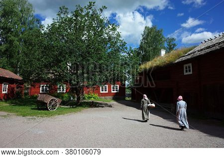 Vasteras, Sweden - Jul 03, 2019: Vallby open-air Museum. Two women in old style swedish clothes walking among traditional wooden red houses. Summer sunny day