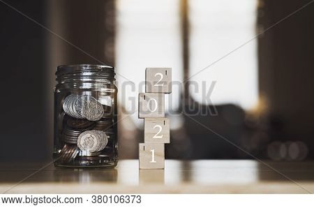 English Pound String Coin And Pennies Nickels In Jar With 2021 On Wooden Stack With Blurry Backgroun
