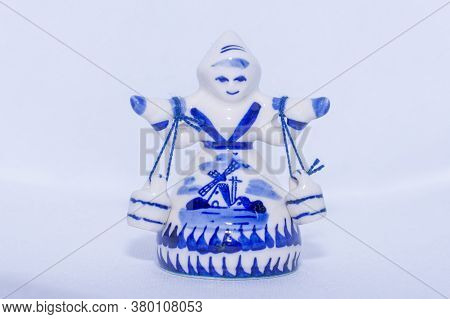 Delft Blue Figurine Of Girl Carrying Bells. Souvenir From Holland/netherlands On Isolated White Back