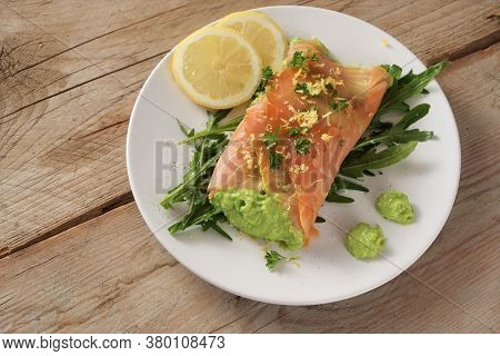 Smoked Salmon Filled With Pea Puree On Arugula Salad With Lemon Slices And Parsley Garnish On A Rust