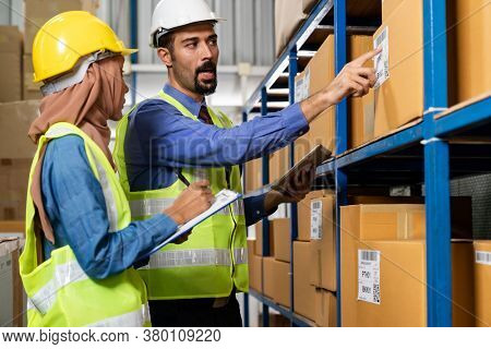Middle east turkish white warehouse manager talk to Islam asian warehouse worker about inventory logistic route in distribution center. For business warehouse inventory and logistic concept.