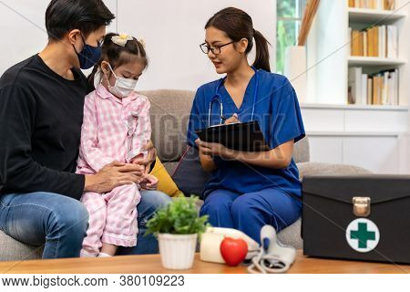 Asian female doctor examine symptoms to little girl patient child sit with her father in living room while doctor visit at home. Home health care delivery and doctor visiting concept.