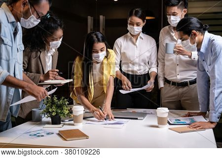 Work late concept of Interracial asian business team brainstorm idea at office meeting room at night. They wear face mask reduce risk to infection of COVID-19 coronavirus as new normal lifestyle.