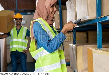 Asian Islam Muslim female warehouse worker do inventory with barcode scanner with Indian worker hold cardboard box in warehouse distribution. For business warehouse inventory and logistic concept.